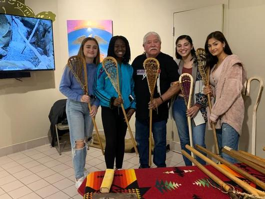 This is a photo of four Nottingham girls and a lacrosse stick maker, each holding a lacrosse stick.